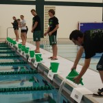 """Team members from the Boys and Girls Swim Teams participate in the """"Pouring of Waters"""""""