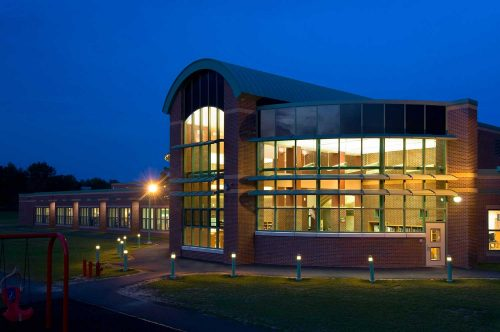 Shatekon Elementary School design at night. By Mosaic Associates Architects.