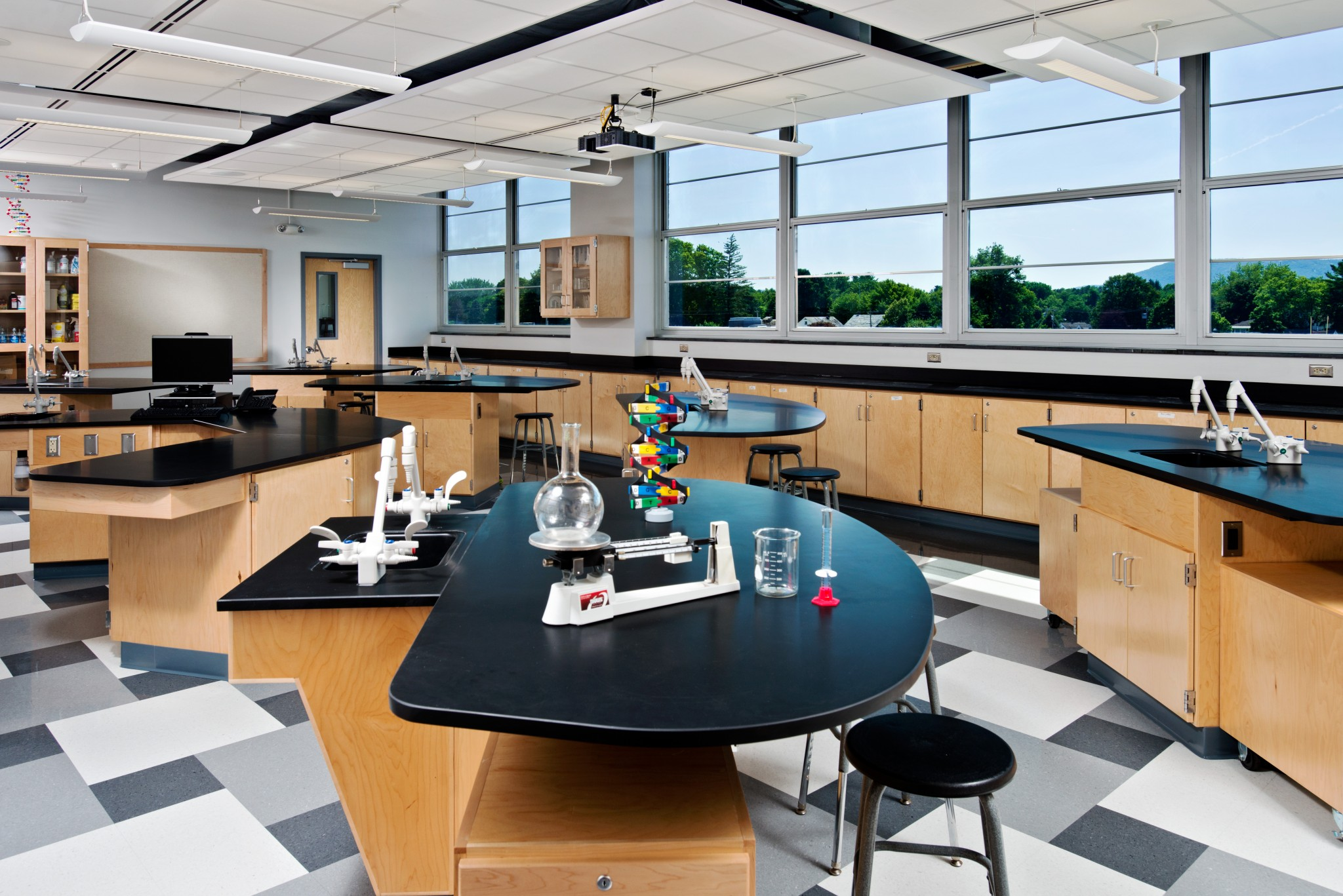 """Mosaic Associates used of """"teaching walls"""" in the Glens Falls High School science wing to define laboratory and instructional spaces in the long classrooms, while larger tables are designed to serve as both lab tables and student desks."""